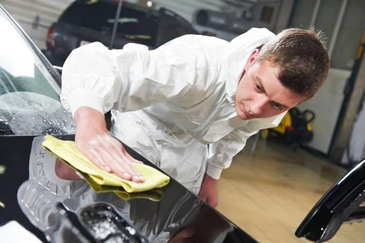 man wiping off car spots