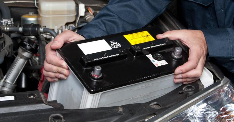 car mechanic replacing car battery VRLA car battery