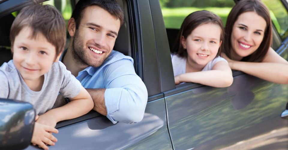 man and his family smiling in car