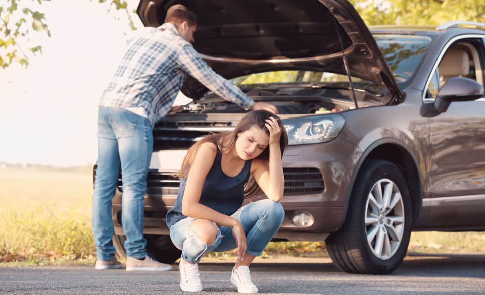 man and woman with broken car