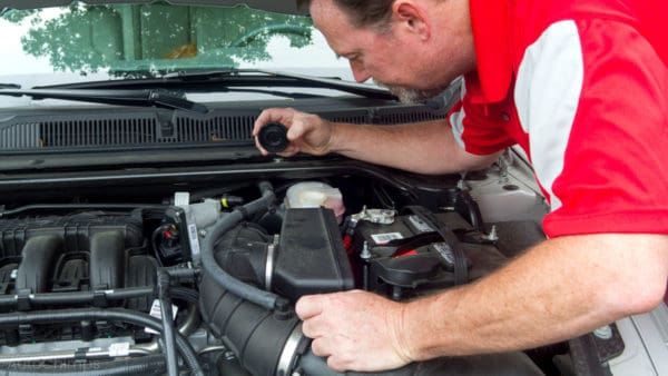man checking car brake master cylinder