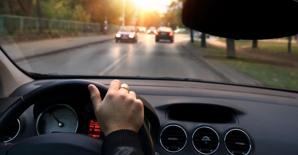 man in car driving through street