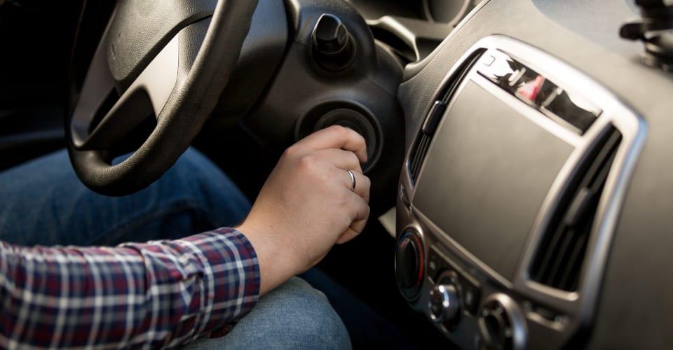 man inserting key in car ignition lock