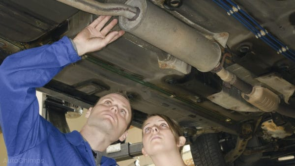 car mechanics looking at car muffler or exhaust system