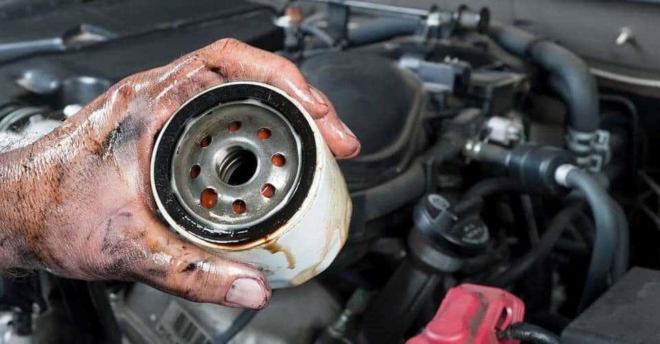 mechanic holding oil filter